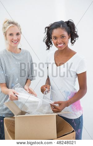 Cheerful housemates unpacking moving boxes and smiling at camera in new home