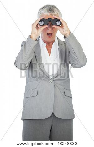 Astonished businesswoman looking at something through binoculars on white background