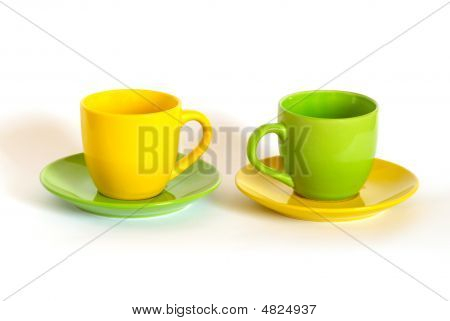 Two Colored Tea Cups And Saucers On White Background.