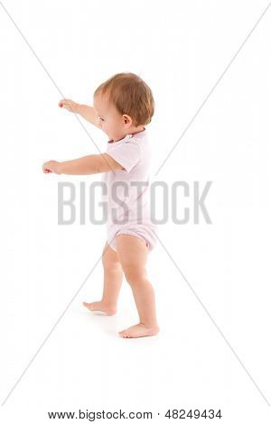 Cute baby girl making first steps, balancing.