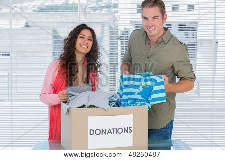 Smiling volunteers taking out clothes from donations box for a charity