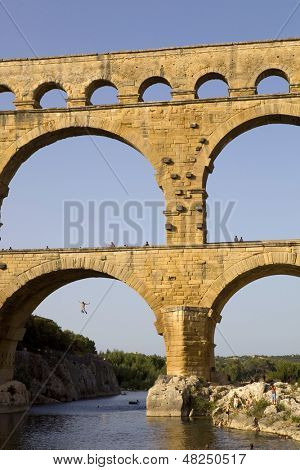 PONT DU GARD, FRANCE - AUGUST 18: A man jumps from the Famous Pont du Gard, Roman aqueduct, on August 18, 2012 in Pont du Gard, Remoulins, Gard, France.