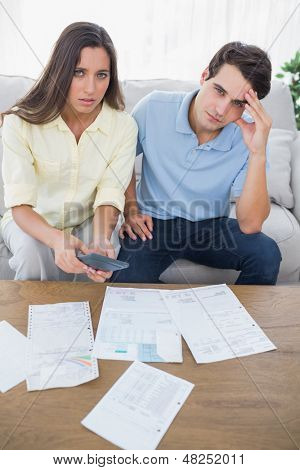 Concerned couple doing their accounts sat on a couch