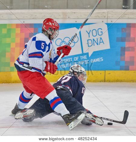INNSBRUCK, AUSTRIA - JANUARY 18 Egor Orlov (Russia) and Jack Eichel (USA) fight for the puck as Russia beats the USA 7:1 in the men's ice hockey tournament on January 18, 2012 in Innsbruck, Austria.