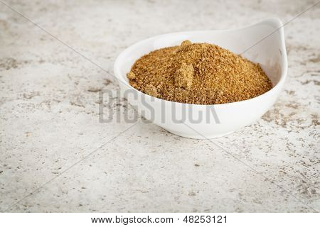 small ceramic bowl of unrefined coconut palm sugar against a ceramic tile background with a copy space