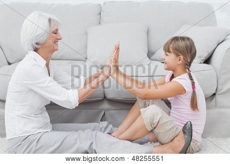 Little girl and grandmother playing together while they are sat on a carpet in the living room