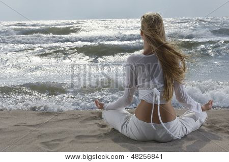 Rear view of a young woman meditating on beach facing the ocean