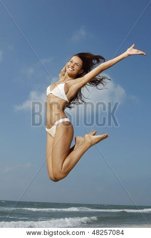 Full length of a cheerful young woman in bikini jumping midair on beach