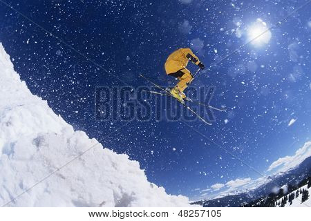 Low angle view of a skier in midair above snow on ski slopes