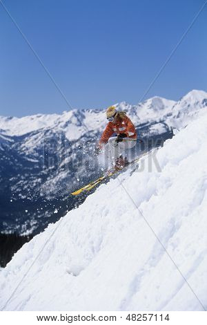 Side view of a skier skiing down ski slope against mountain and clear blue sky