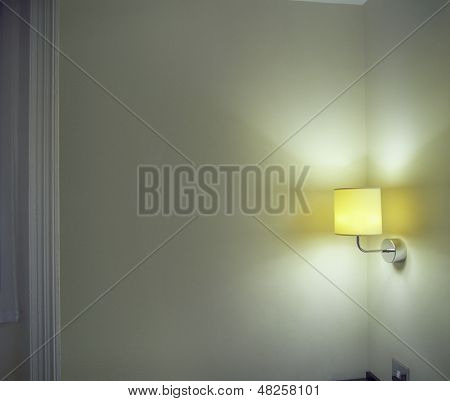 Closeup of lit sconce shining light onto corner wall in the room