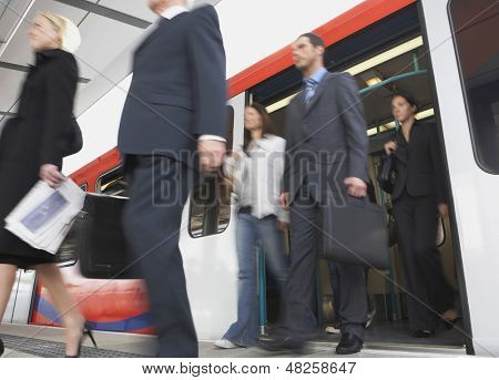 Low angle view of business commuters getting off a train
