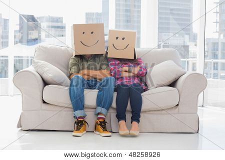 Silly workers wearing boxes on their heads with smiley faces on a couch