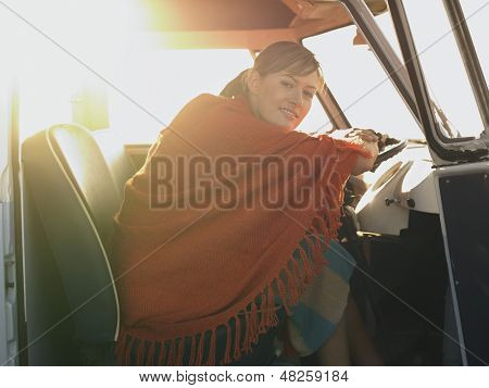Portrait of happy young woman wrapped in shawl sitting at driver's seat of van