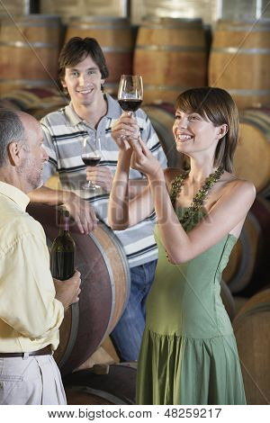 Three people tasting wine beside wine casks in cellar