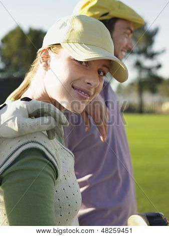 Portrait of happy young female golfer with friends on golf course