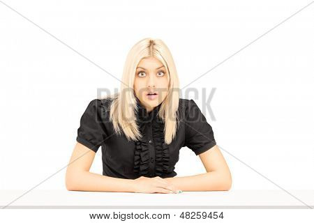 Surpised young woman sitting on a table isolated on white background