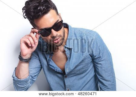 closeup of a casual young man holding a hand on his sunglasses while looking away from the camera. on gray background
