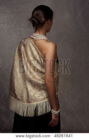 beautiful woman in gold shawl and black dress standing with her back on grunge texture background wearing expensive pearl necklace