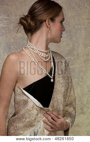 beautiful woman in gold shawl and black dress looking over her shoulder on grunge texture background wearing expensive pearl necklace