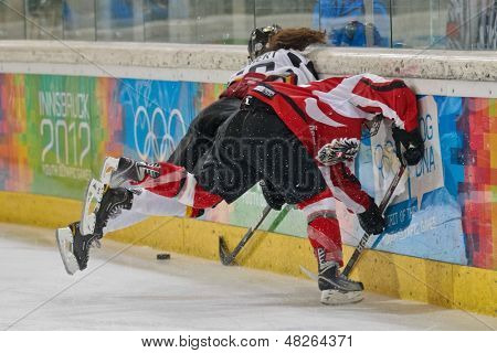 INNSBRUCK, AUSTRIA - JANUARY 20 Anna Fiegert (Germany) and Paulina Polczik (Austria) fight for the puck in the ice hockey tournament on January 20, 2012 in Innsbruck, Austria.