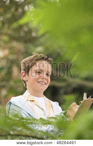 Happy young boy writing on clipboard in forest during field trip