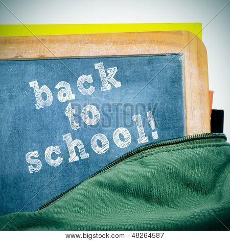 sentence back to school written in a blackboard with a wooden frame, in a schoolbag, with a retro effect