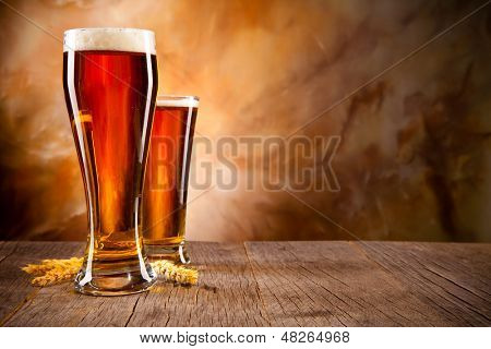 Glasses of beer on wood
