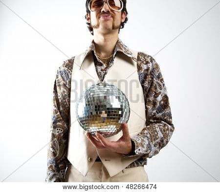 Portrait of a retro man in a 1970s leisure suit and sunglasses holding a disco ball - mirror ball