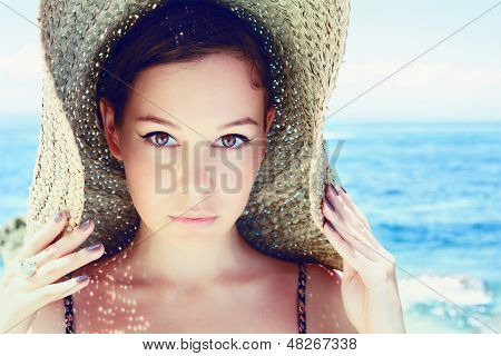 Young, beautiful  woman wearing a straw hat on the beach