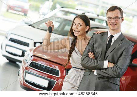 Casal jovem feliz com as chaves do carro novo, após a compra de automóvel no showroom de revendedor