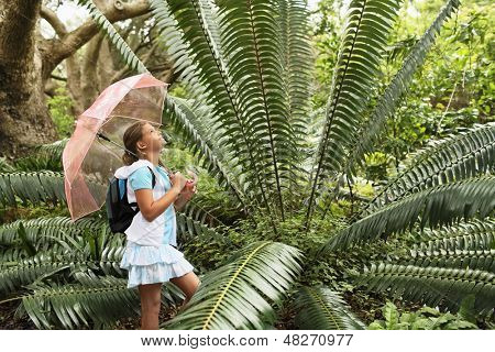Side view of young girl with umbrella looking at large fern in forest