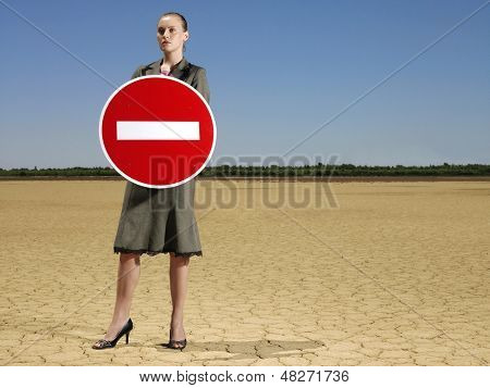 Full length of young businesswoman holding 'No Entry' sign in barren landscape