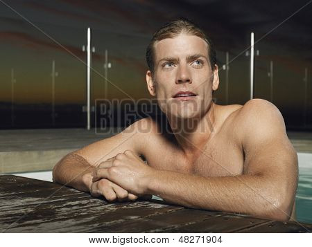 Closeup of a young shirtless man leaning on edge of outdoor pool at dusk