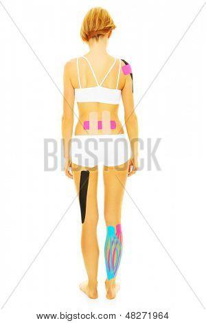Uma foto das costas de uma mulher com fita de fisio em diferentes partes do corpo dela sobre backgrou branco