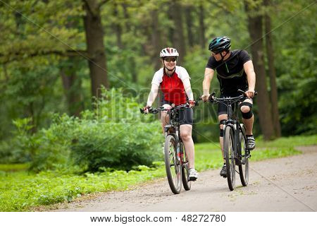 happy Man and woman exercising with bicycles outdoors, they are a couple in park