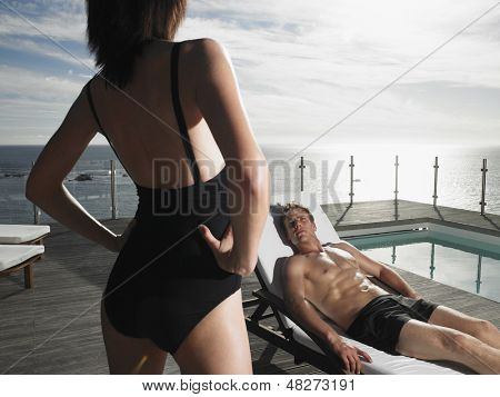 Man reclining on deckchair and looking at woman by pool and sea