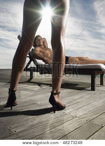 Man reclining on deckchair and looking up at woman on a sunny day