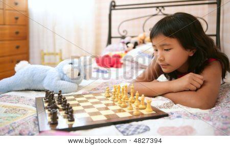 Asiatische Mädchen spielt Schach mit Teddy Kaninchen