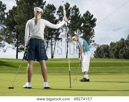Male golf player putting on green with female golfer holding flag in foreground