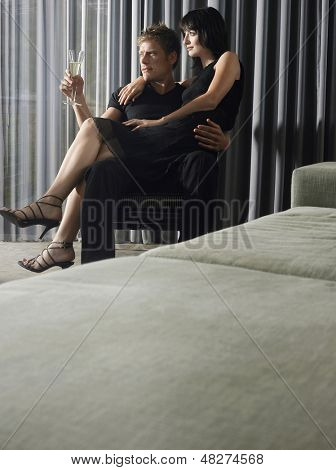 Young woman sitting on man's lap in the living room