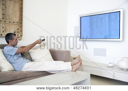 Full length of middle aged man using TV remote in living room