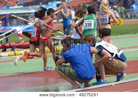 DONETSK, UKRAINE - JULY 12: Cameramen film girls competing in 2000 m steeplechase during 8th IAAF World Youth Championships in Donetsk, Ukraine on July 12, 2013