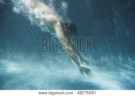 Side view of middle aged man swimming underwater