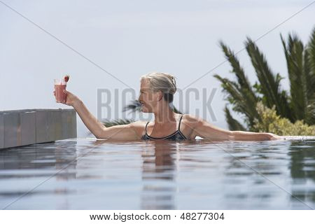 Happy middle aged woman placing daiquiri on poolside from pool