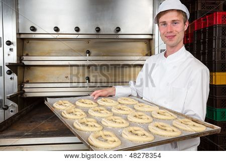 Baker In Bakery With Baking Plate Full Of Pretzels