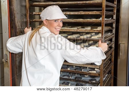Baker Pushing Rack Full Of Bread Into The Oven