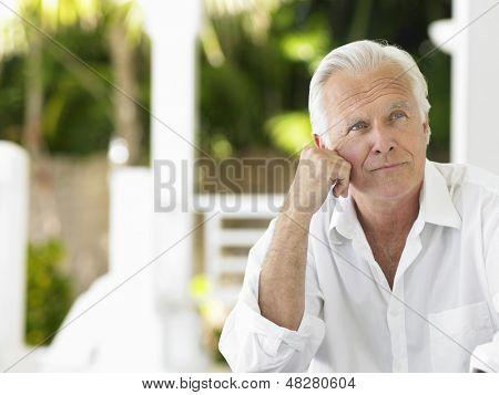 Portrait of a thoughtful mature man sitting on verandah