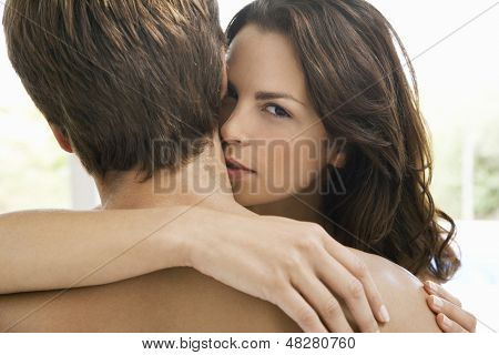 Portrait of romantic young woman kissing on man's neck