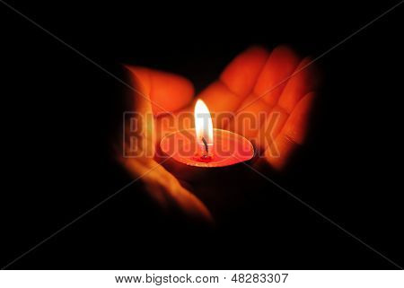 Left Hand Holding A Burning Candle In Dark